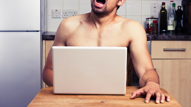 man pulling orgasm face while sitting behind a laptop