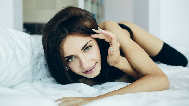 sexy woman laying on bed looking at the camera