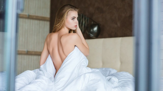woman on bed in covers