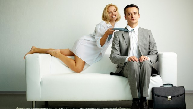 woman seducing man on sofa by pulling his tie
