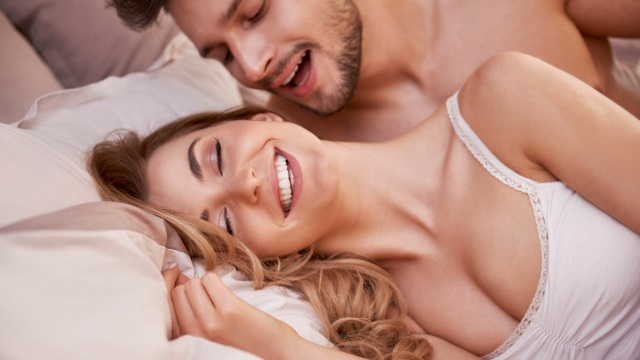 man whispering in womans ear on bed
