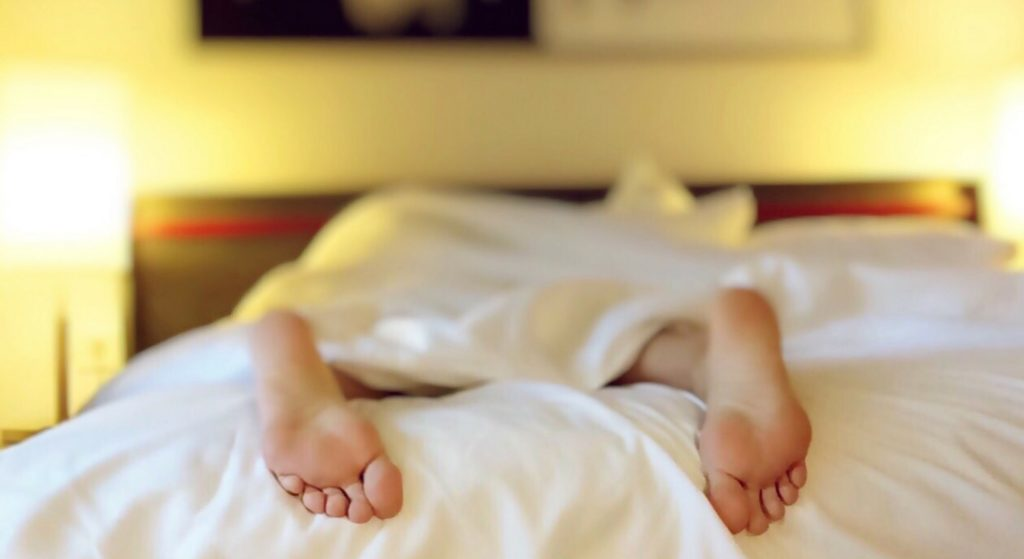 man in bed with his feet hanging off the bed