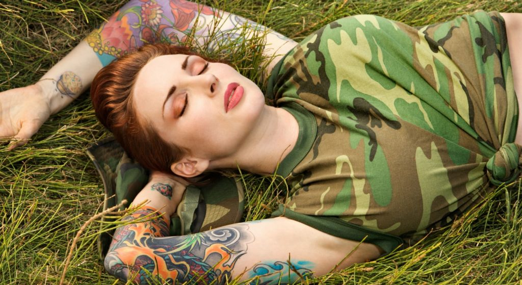 tattooed woman laying on field
