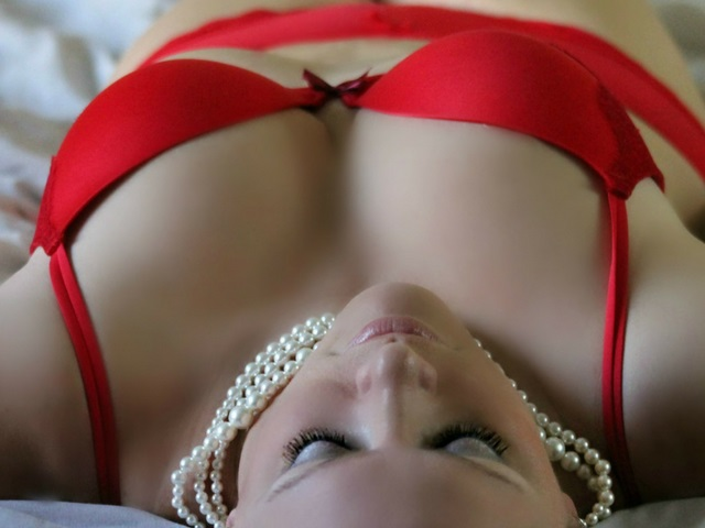 woman in red bra laying on bed