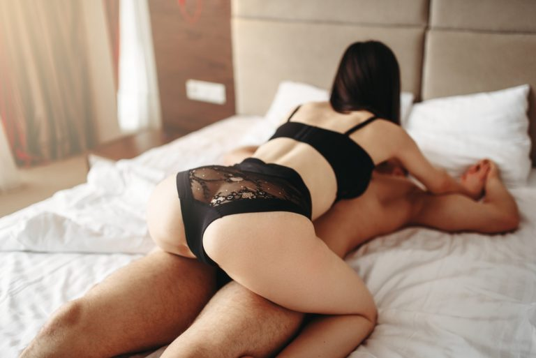 Woman and man cuddling on bed