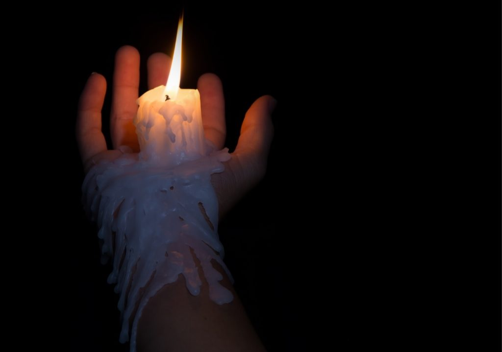 person trying wax play melting candle on thier hand